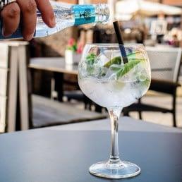 groot glas met een gin tonic op het terras van Restaurant Bij5 in het Westland