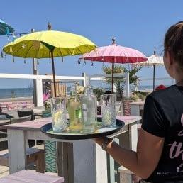Suzanna met dienblad met drankjes op de rug gezien bij strandtent Bugaloe Beach in het Westland