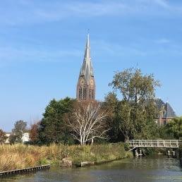 Uitzicht over het water op de kerktoren van de Sint-Bartholomeuskerk in Poeldijk in het Westland
