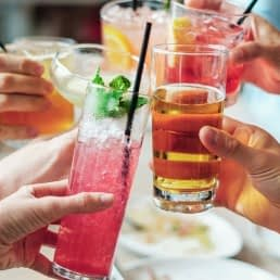 foto's van handen die met een kleurige cocktail in hun hand proosten in het Westland