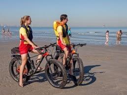 twee lifeguard medewerkers van de Reddingsbrigade 's-Gravenzande patrouilleren per fiets op het strand van het Westland