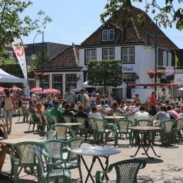 terrassen met tafels en stoelen en mensen die genieten van de zon op het Marktplein in 's Gravenzande in het Westland
