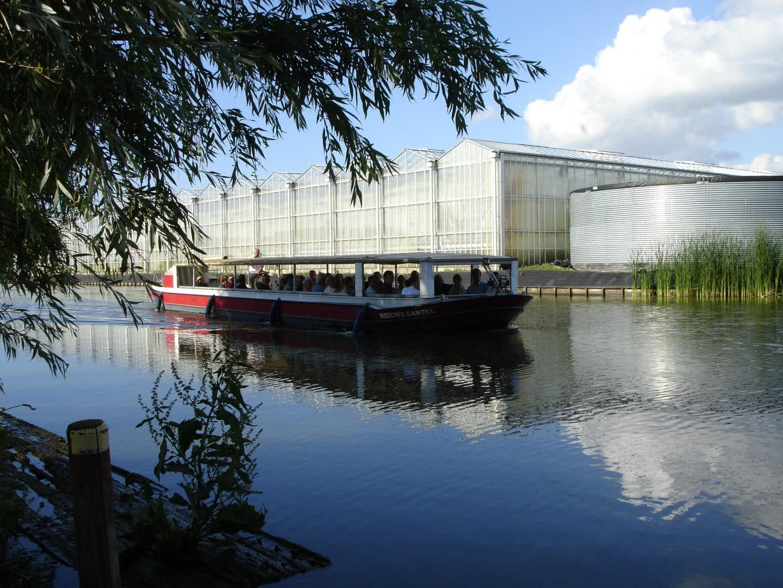 rondvaartboot van Rondvaartbedrijf de gantel vaart langs glazen kassen in het westland