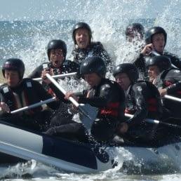 Groep volwassenen varen in een rubberen raftboot in de branding van de zee met opspattend water in het Westland
