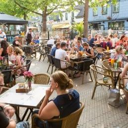 zomers terras vol met jonge mensen en gezinnen die genieten van eten en drinken in 's Gravenzande in het Westland