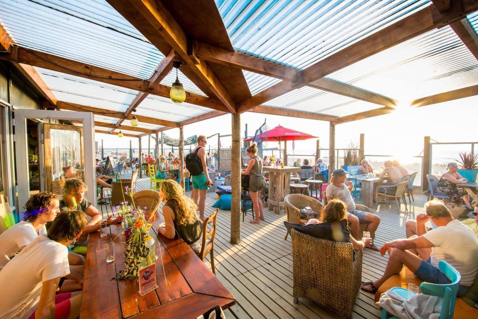 zonnig terras vol gasten van Dreams Beachhouse op het strand van Ter Heijde in het Westland