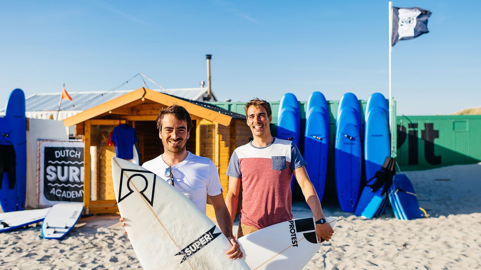 eigenaren Kaspar Hamminga & Erik Ringelberg op de foto met surfplanken in de hand voor hun surfschool Dutch Surf Academy op het strand in het Westland