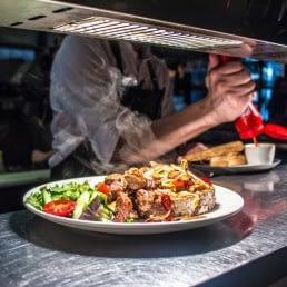 bord dampend warm eten staat klaar om uitgegeven te worden vanuit de keuken van Brasserie Mirell in het Westland
