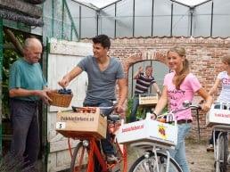 Twee jongens en twee meisjes die met de fiets met voorop een houten kratje stoppen bij een glazen druivenkas om druiven te halen tijdens de fietstocht Bakkie Fietsen in het Westland