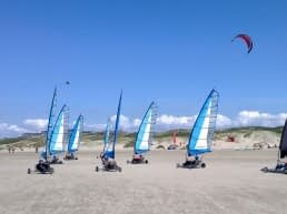 blokarts van beachline beach rijden over het strand van het Westland op een zonnige dag met in de achtergrond meerdere powerkites