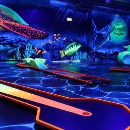 Indoor minigolfbaan met fluoriscerende verlichting en versiering alsof je onder water bent met haaien en schildpadden bij Van der Ende Racing Inn in het Westland