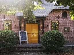entree van familiehotels in een oude boerderij met rieten dak en gele deuren en twee buxus hagen naast de deur in het Westland