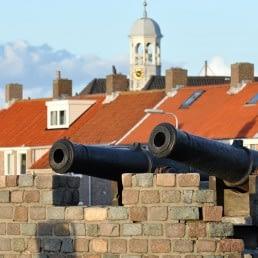 foto van twee antieke kanonnen bij het momument voor Admiraal Tromp in Ter Heijde in het Westland met op de achtergrond huisjes met rode daken aan de kust in het Westland
