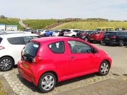 parkeerplaats vol met geparkeerde auto's aan het strand in het westland