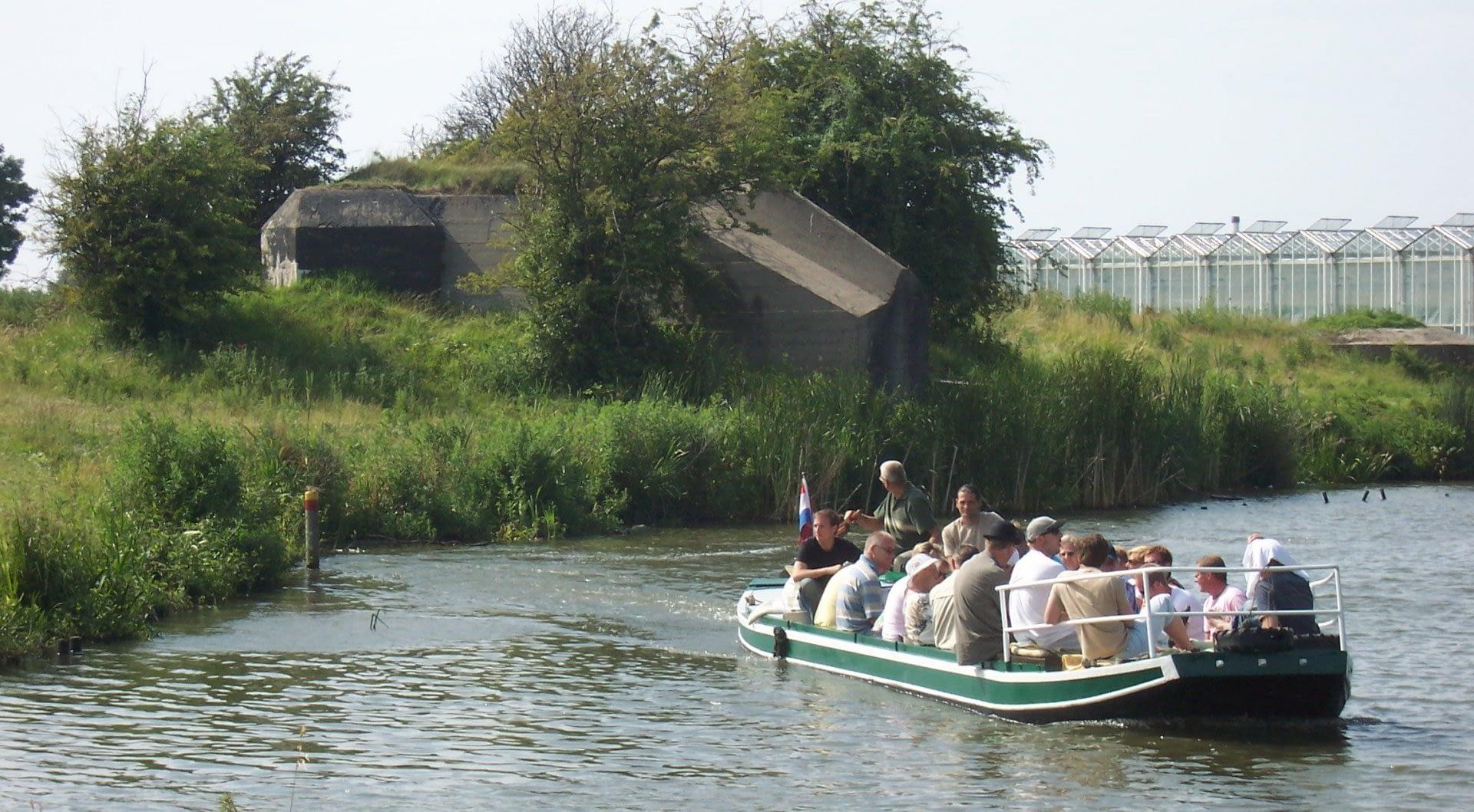 bootje met mensen aan boord vaart langs bunkers tussen de glazen kassen in het Westland