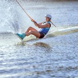 jonge vrouw op een wakeboard op het water voortgesleept door de kabelbaan van Wollebrand Cablepark in het Westland