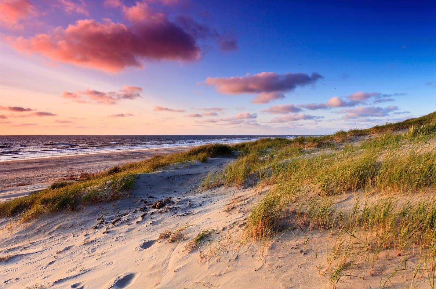 foto van zandduinen in het Westland begroeid met groen helmgras en in de achtergrond de zee met wolken en een rode gloed van de zon