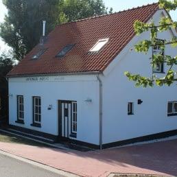 Vrijstaand wit vakantiehuisje met rood dak met de naam Antonius Hoeve onderaan de dijk bij Paviljoen de Zweth in het Westland