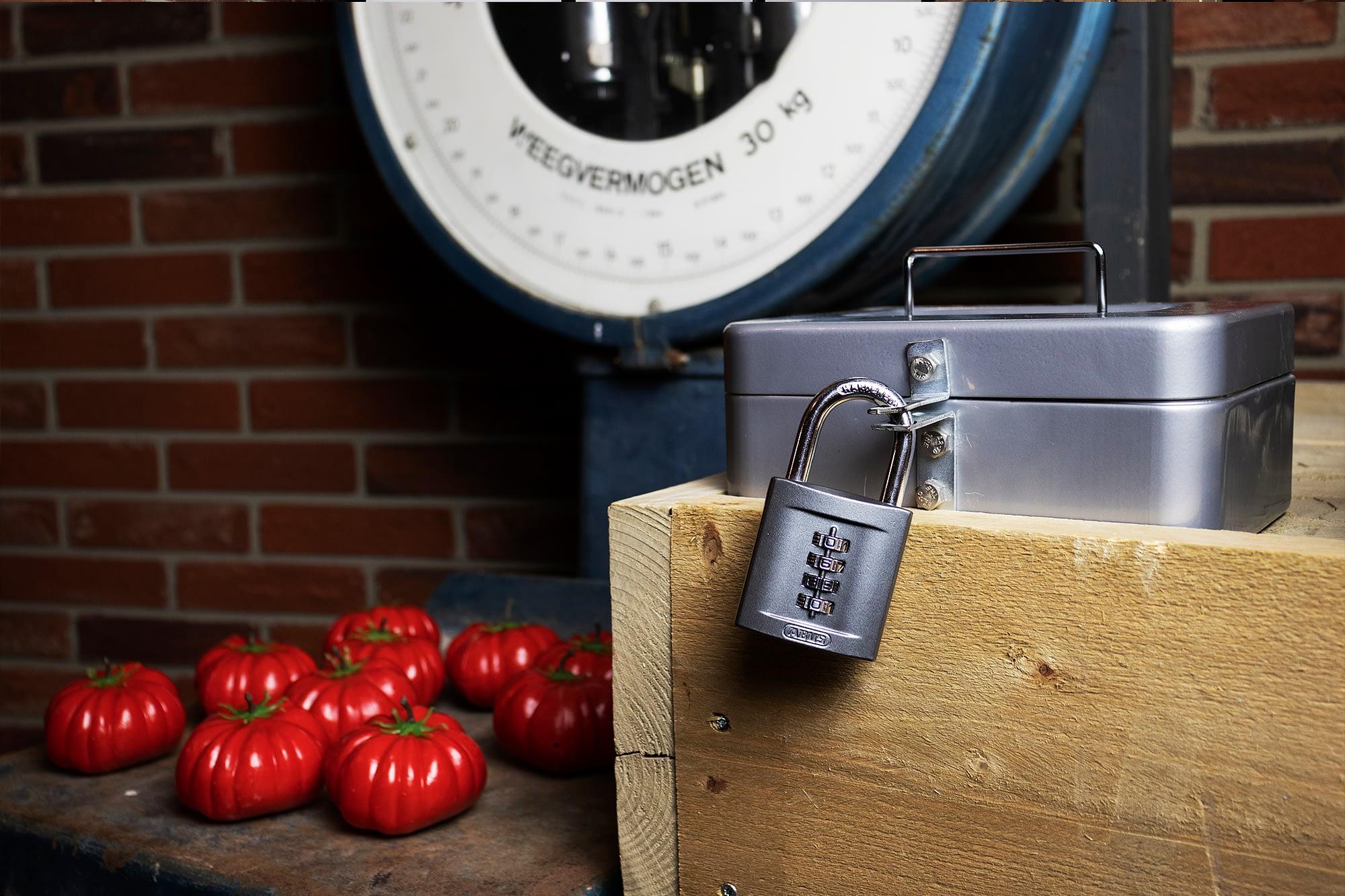 Geldkistje met cijferslot, weegschaal en grote rode tomaten in de escaproom van Ac Escape in het Westland