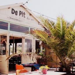 buitenzijde van Strandtent De Pit met terras en palmvaren op een zonnige dag