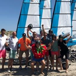 groepje juichende mannen staat op het strand in het Westland voor blokarts met blauw witte zeilen op een zonnige dag