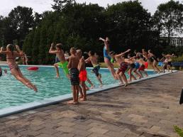 grote groep kinderen die op een warme zomerse dag met zijn allen tegelijk in het buitenbad van Zwembad De Hoge Bomen springen in het Westland