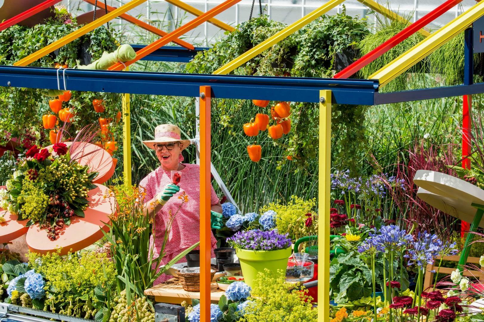 tuinder op een met bloemen en planten versierde boot tijdens het Varend Corso in het Westland