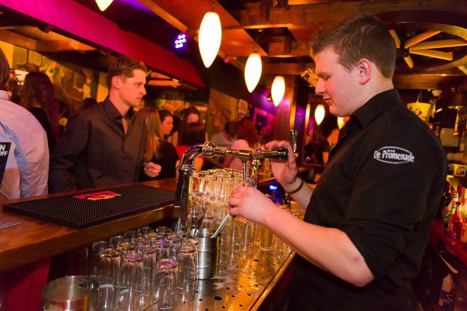barman tapt bier achter de basr van bar de Promenade in het Westland