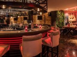 bar van Hotel Restaurant Unicum Elzenhagen in het Westland met hoge barstoelenn, een rond bar en rode ledverlichting