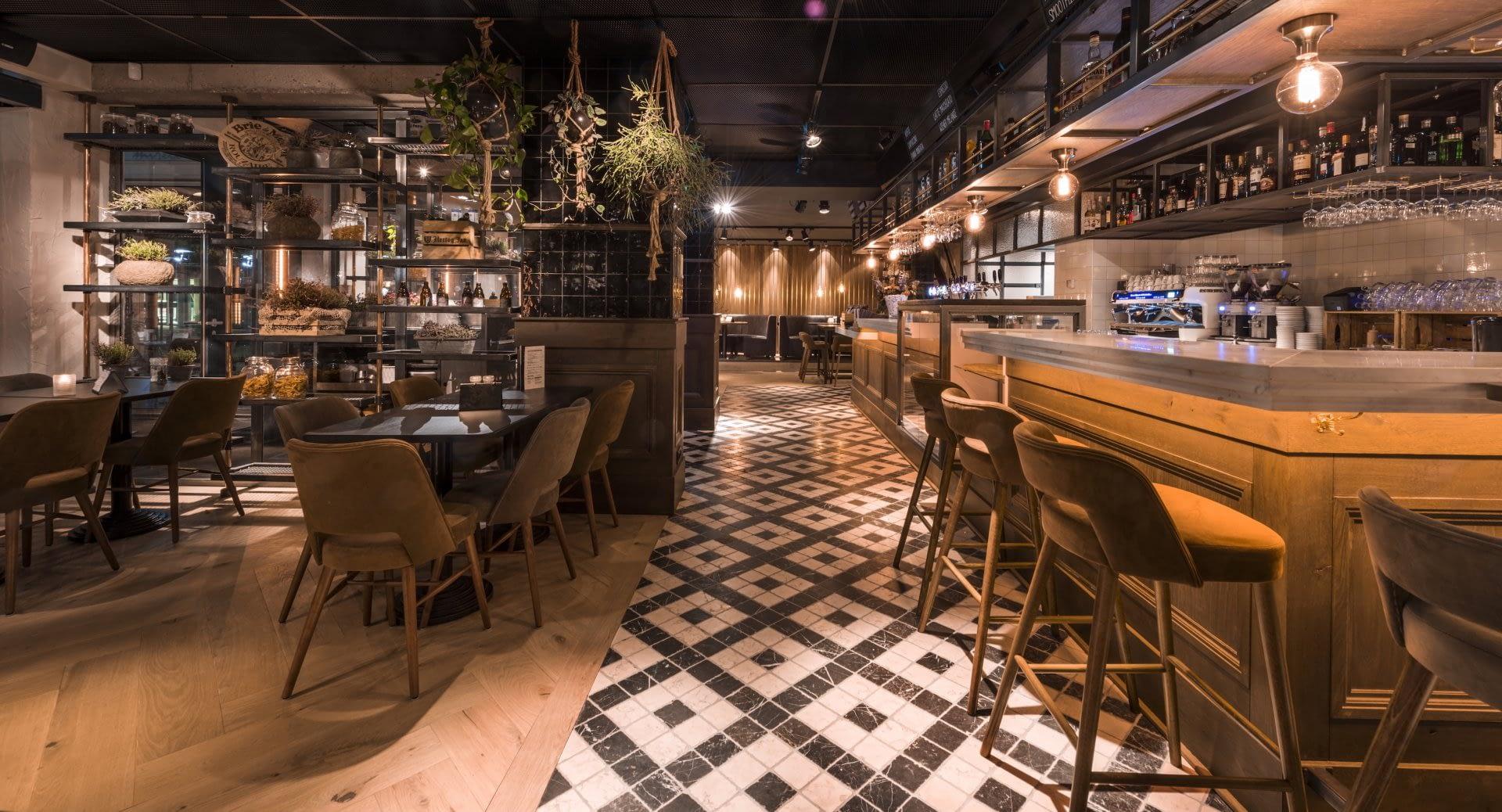 interieur van brasserie Mirell in Naaldwijk met mozaik vloer, houten bar en tafeltjes