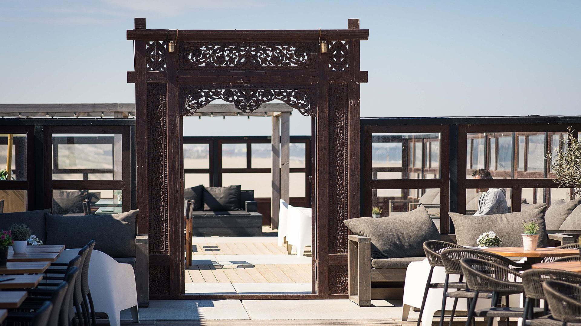 buitenterras van strandtent Bondi Beach Club in Monster in het Westland met gedekte tafels en een fraai Balinese teakhouten deur met snijwerk en uitzicht op zee