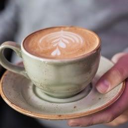 hand met kopje koffie in een groen kopje bij NON Bar in het Westland