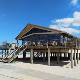 Strandtent The Coast in Monster aan de Westlandse kust in een houten gebouw op palen hoog boven het strand op een zonnige dag met blauwe lucht en een leeg strand