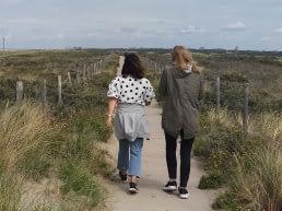 Twee vrouwen lopen naast elkaar door de duinen aan de Westlandse kust met in het midden een wandelpad en links en rechts met helmgras begroeide duinen