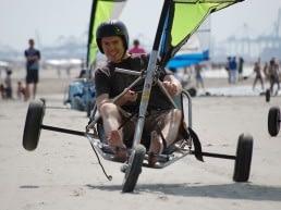 man in blokart scheurt over op het strand in het Westland recht op de fotograaf af bij Wato Events