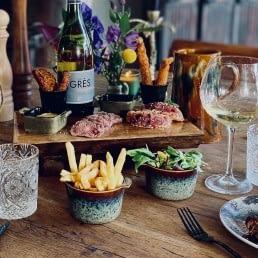 tafel met bordjes met spareribs en kleine gerechtjes als shared dining bij Bistro De Herberg in het Westland